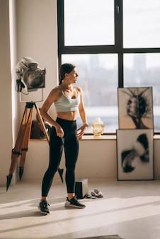 Mooie jonge vrouw voert oefeningen thuis uit