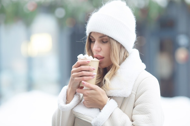 Mooie jonge vrouw warme chocolademelk buitenshuis drinken. kerstmis.