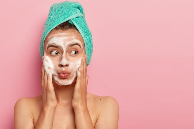 Mooie jonge vrouw wast gezicht met zeep, houdt lippen rond, kijkt opzij op kopie ruimte, reinigt teint van vuil, neemt een bad, droogt het haar met een handdoek, toont naakt lichaam