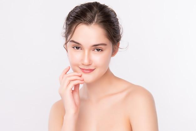 Mooie jonge vrouw wat betreft haar schoon gezicht met verse gezonde geïsoleerde huid, schoonheidsschoonheidsmiddelen en gezichtsbehandelingsconcept.