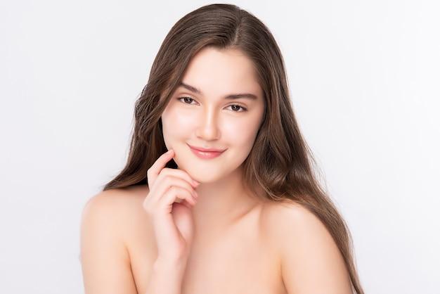 Mooie jonge vrouw wat betreft haar schoon gezicht met verse gezonde geïsoleerde huid, schoonheidsschoonheidsmiddelen en gezichtsbehandelingsconcept