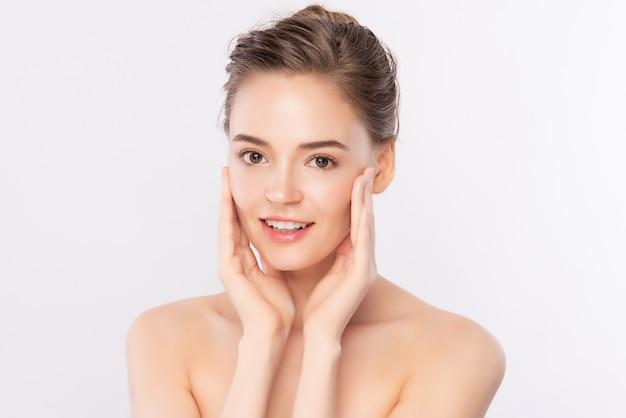 Mooie jonge vrouw wat betreft haar schoon gezicht met verse gezonde huid, die op wit wordt geïsoleerd
