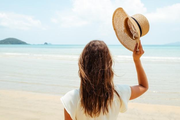 Mooie jonge vrouw werpt haar hoed op een zonnig strand