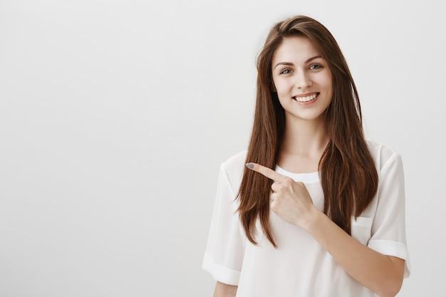 Mooie jonge vrouw wijzende vinger naar links, glimlachend als uitnodigende blik op copyspace