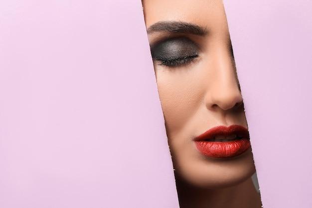 Mooie jonge vrouw zichtbaar door gesneden kleurenpapier