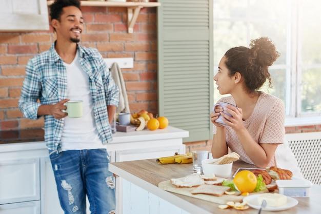 Mooie jonge vrouw zit aan de keukentafel, houdt mok hete thee,
