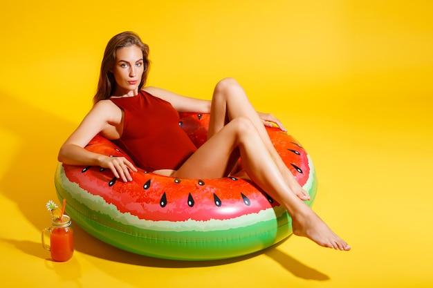 Mooie jonge vrouw zit in opblaasbare watermeloen ring met cocktail geïsoleerd op gele achtergrond