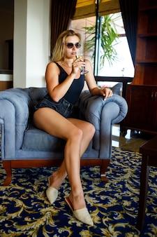 Mooie jonge vrouw zit op een zachte fauteuil in de lobby van het hotel met een glas champagne op vakantie. ze draagt een zonnebril en een glimlach op haar gezicht. vakantie concept