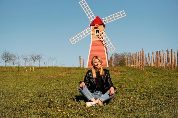 Mooie jonge vrouw zit op het gras tegen de achtergrond van de rode molen.