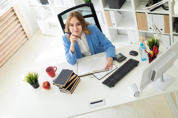 Mooie jonge vrouw zitten aan de balie in kantoor, een pen in haar hand houden en een boek lezen.