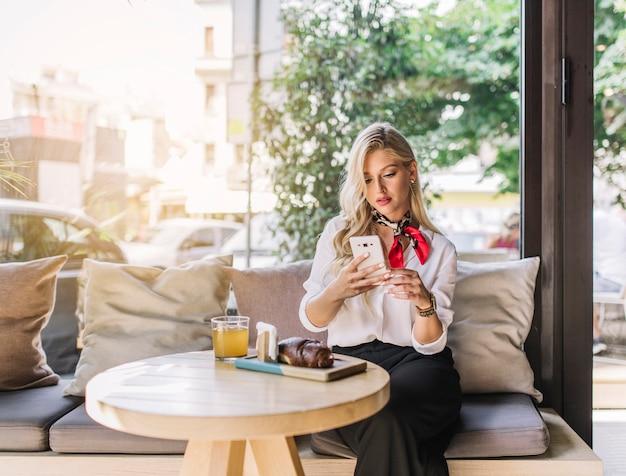 Mooie jonge vrouw zitten in de caf� met behulp van de mobiele telefoon