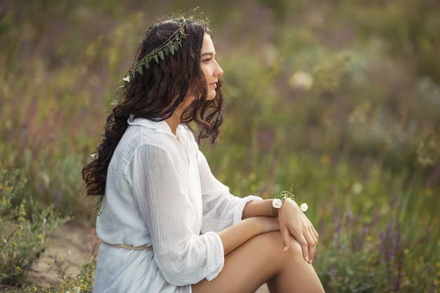 Mooie jonge vrouw zitten in een tarweveld in de zomer zonsondergang. schoonheid en zomerconcept