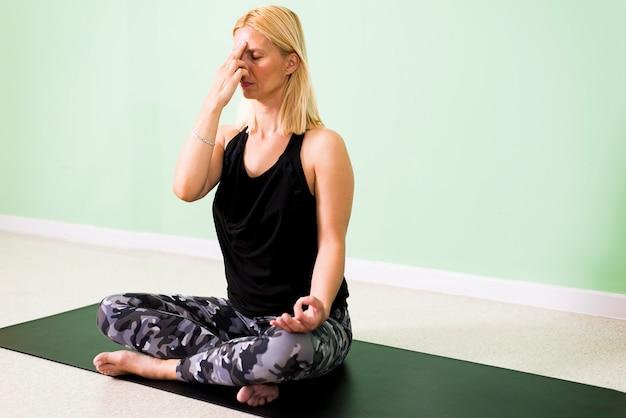 Mooie jonge vrouw zitten in yoga positie en mediteren