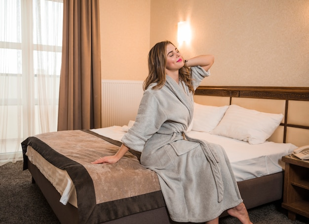Mooie jonge vrouw zittend op bed die zich uitstrekt glimlachen