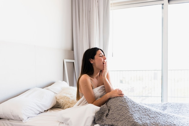 Mooie jonge vrouw zittend op bed geeuwen