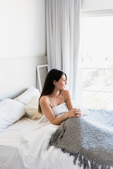 Mooie jonge vrouw zittend op bed met grijs tapijt