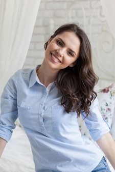Mooie jonge vrouw zittend op bed