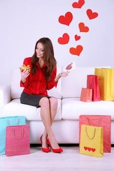Mooie jonge vrouw zittend op de bank met boodschappentassen en geschenkdoos op grijze achtergrond