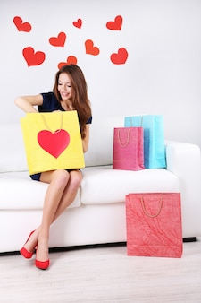 Mooie jonge vrouw zittend op de bank met boodschappentassen op grijze achtergrond
