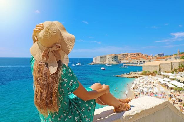 Mooie jonge vrouw zittend op de muur kijken naar een prachtig uitzicht op de middellandse zee en de oude stad dubrovnik in kroatië, europa. levensstijl vrouw met strooien hoed dragen groene jurk genieten van uitzicht op het landschap.
