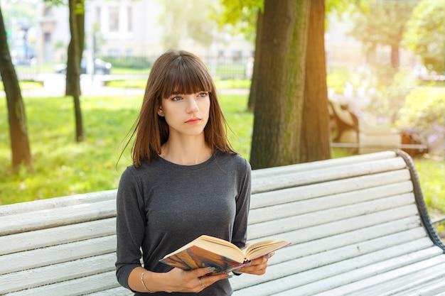 Mooie jonge vrouw zittend op een bankje in de straat een boek te lezen.