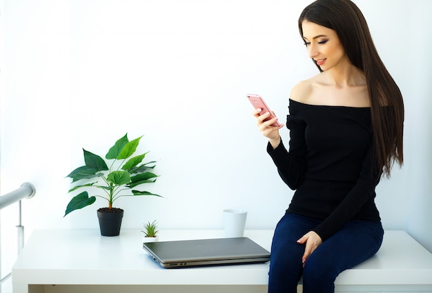 Mooie jonge vrouw zittend op een bureau met een map en een telefoon.