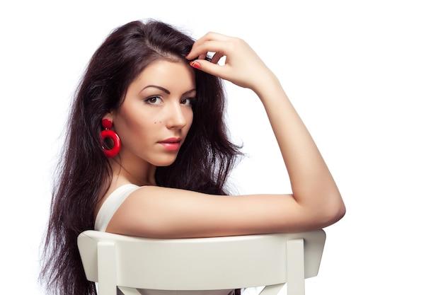 Mooie jonge vrouw zittend op een stoel, close-up, geïsoleerd op wit