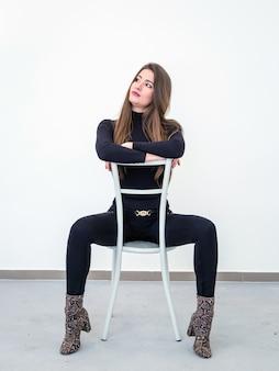 Mooie jonge vrouw zittend op een stoel over witte muur