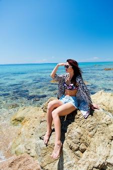 Mooie jonge vrouw zittend op grote steen op het strand in griekenland