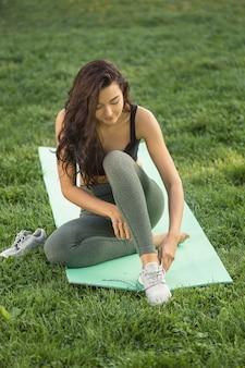 Mooie jonge vrouw zittend op yogamat buitenshuis en schoenveters koppelverkoop op sneakers. gezond