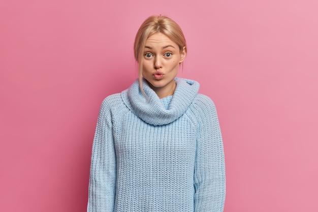 Mooie jonge vrouw zonder make-up blond gekamd haar en blauwe ogen pruilen lippen en ziet er verrassend uit Gratis Foto