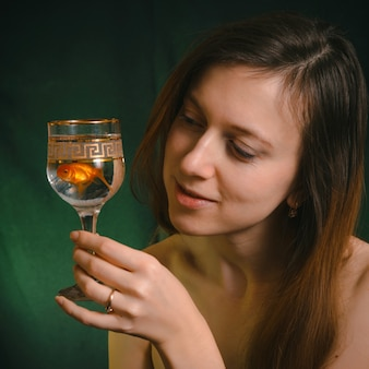 Mooie jonge vrouw zonder make-up die een gouden vis in het glas houdt en wens doet