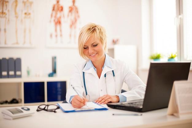 Mooie jonge vrouwelijke arts die op haar kantoor werkt