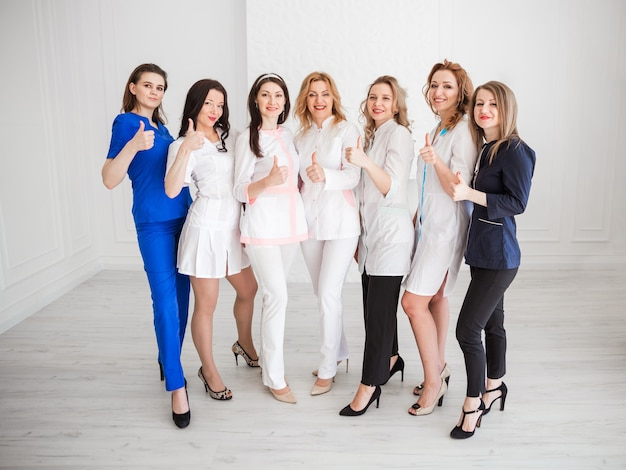 Mooie jonge vrouwelijke artsen in witte uniformen poseren tegen de achtergrond van een witte muur, tonen de klas met hun hand en kijken naar de camera en glimlachen.