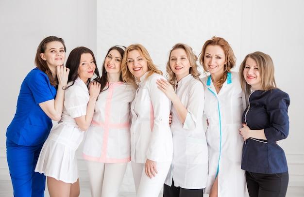 Mooie jonge vrouwelijke artsen in witte uniformen poseren tegen de achtergrond van een witte muur. vrouwen knuffelen als teken van teameenheid.