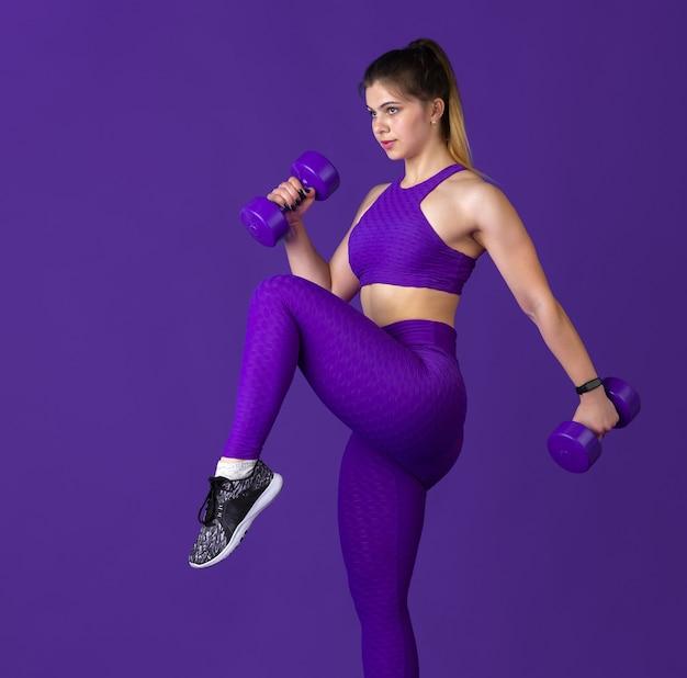Mooie jonge vrouwelijke atleet die met gewichten oefent