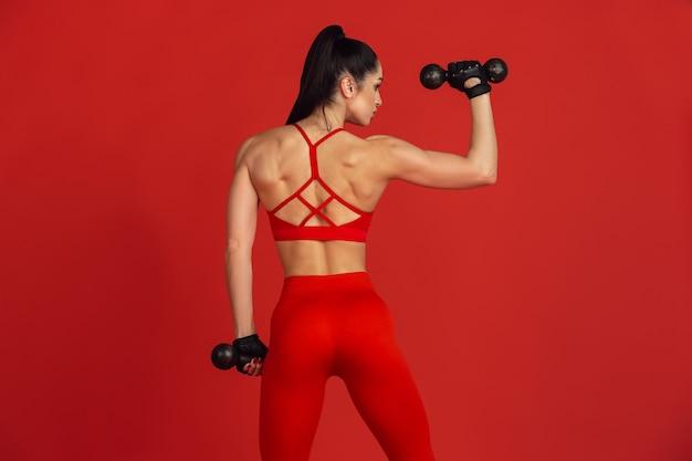Mooie jonge vrouwelijke atleet die op rode studiomuur oefent