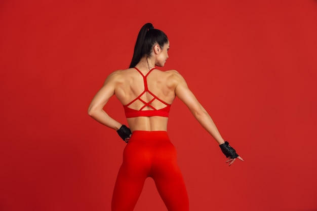 Mooie jonge vrouwelijke atleet die op rood oefent