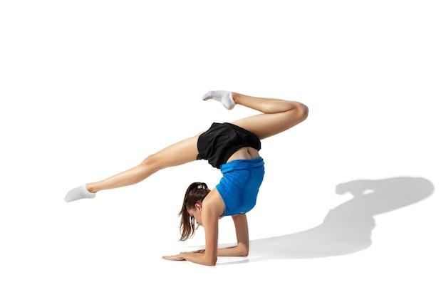 Mooie jonge vrouwelijke atleet die zich uitstrekt, training op witte ruimte, portret met schaduwen