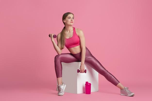 Mooie jonge vrouwelijke atleet oefenen op roze studio muur zwart-wit portret