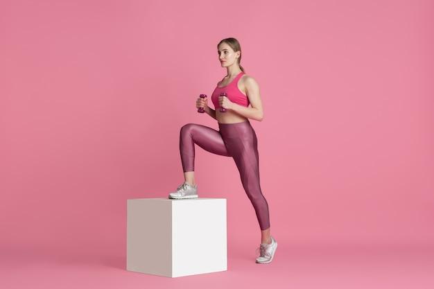 Mooie jonge vrouwelijke atleet oefenen op roze studio