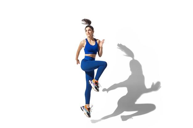 Mooie jonge vrouwelijke atleet oefenen op witte studio achtergrond, portret met schaduwen. sportief fit model in beweging en actie.