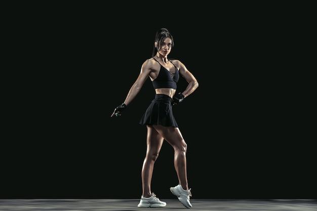 Mooie jonge vrouwelijke atleet oefenen op zwart
