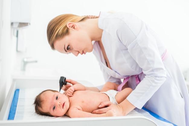 Mooie jonge vrouwelijke blonde arts die weinig baby met oorspeculum onderzoekt in kliniek.