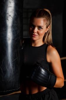 Mooie jonge vrouwelijke bokser staat in de ring bij de bokszak in een oude sportschool, haar handen in bokshandschoenen. vrouw in bokstraining. concept van gezonde levensstijl, sport en lichaamsbeweging in de sportschool. ruimte kopiëren