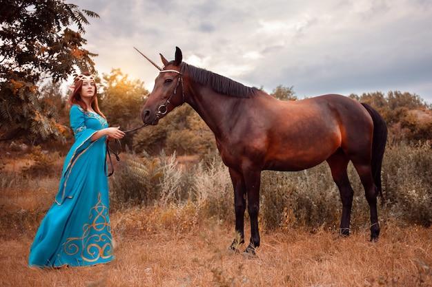 Mooie jonge vrouwelijke elf met lang donker golvend haar aaien haar paard rusten in het bos bos nimf aaien haar paard zorg huisdier liefde dieren harmonie zorgzame eigenaar zacht schepsel mythe