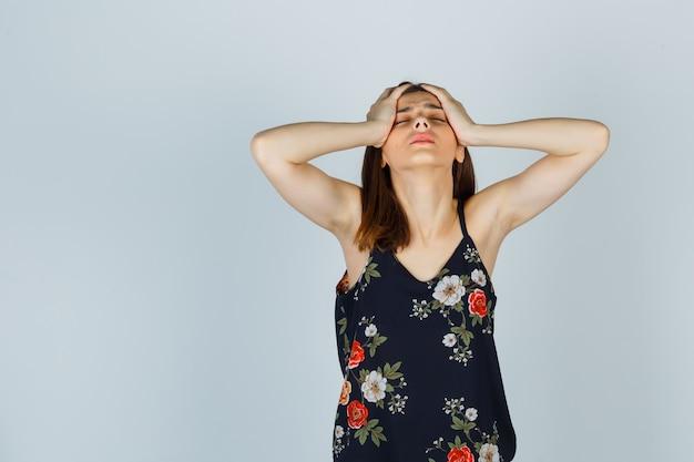Mooie jonge vrouwelijke hand in hand op het hoofd in blouse en vermoeid op zoek