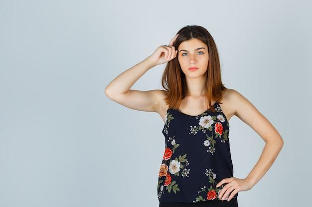 Mooie jonge vrouwelijke hand op het hoofd in blouse houden en nadenkend kijken