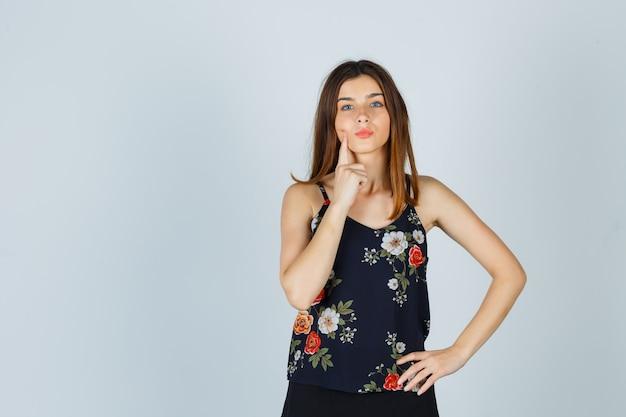 Mooie jonge vrouwelijke holdingsvinger op wang, pruilende lippen in blouse