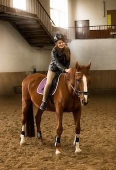 Mooie jonge vrouwelijke jockey die op bruin paard in de manege zit